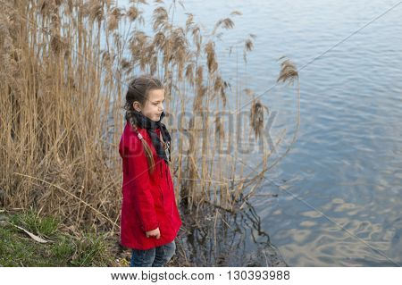 girl in red fashion raincoat near the river with dry reed stalks behind