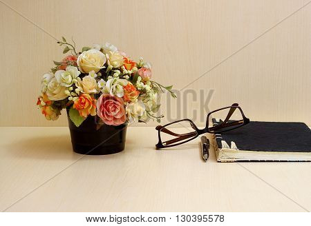 Artificial flowers and set of a black notebook glasses pen on wood table blackground.