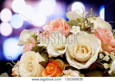 The beautiful artificial flowers on light blurred bokeh background.