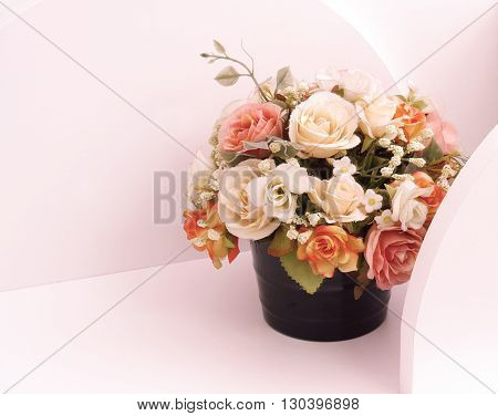 Artificial flowers in flowerpot on white wooden shelves.