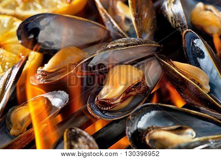Blue mussels on flaming grill with lemon.