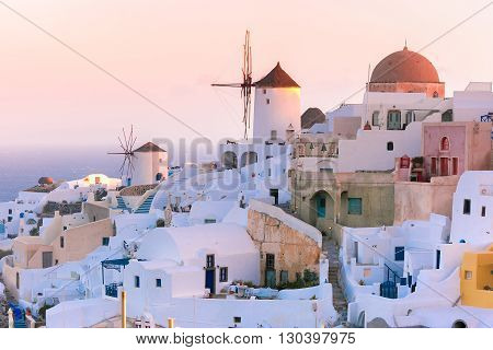 Picturesque famous view, Old Town of Oia or Ia on the island Santorini, white houses and windmills at dawn, Greece