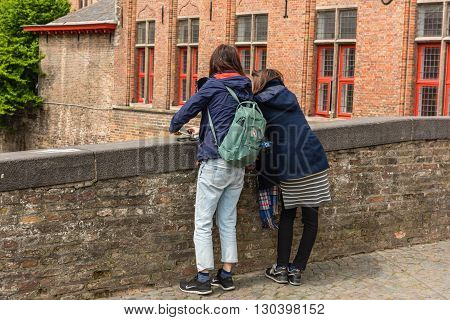 Women Is Taking Pictures On The Street Of Bruges