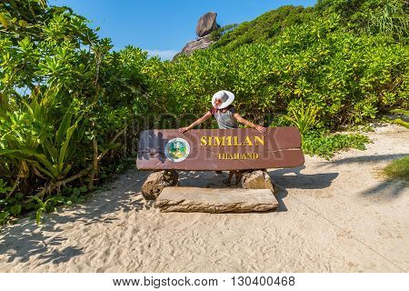 Back of young tourist in front of the sign indicating the famous Kor 8 of Similan Islands National Park, Phang Nga, Thailand, one of the tourist attraction of the Andaman Sea.