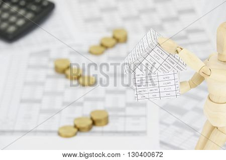 Wooden Dummy Holding House Have Blur Gold Coins With Calculator