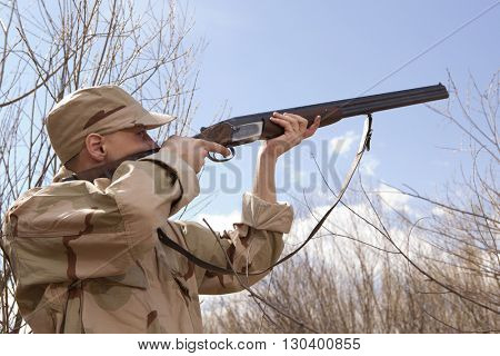 Hunter in camouflage clothes ready to hunt with hunting rifle