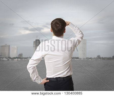 Businessman standing over skyscraper and purposefully looking away