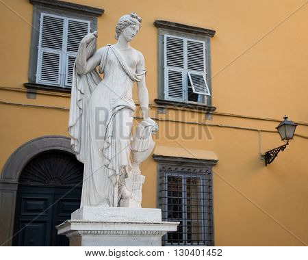 Ancient Statue of a Female Figure - with an amphora atop a water fountain in Piazza Salvatore in the Tuscan village of Lucca Italy.