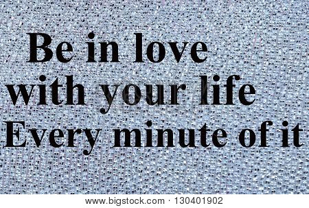 The words Be in love with your life on silver background