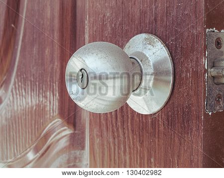 Dusty old door knob on open wooden door vintage effect