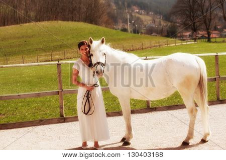 A beautiful girl leads her horse in the paddock