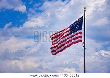 American flag waving with a cloud background.