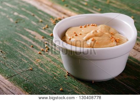 Mustard In White Bowl On Green Wooden Board