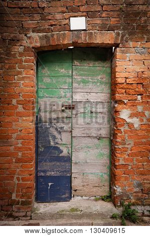 Old wooden door locked with peeling paint in red brick wall (Burano island Venice Italy)