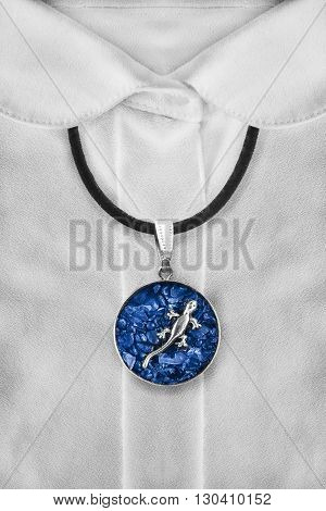 Sapphire medallion on black string on white silk blouse closeup