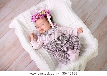 1 month baby girl lies on back looking up and smiling