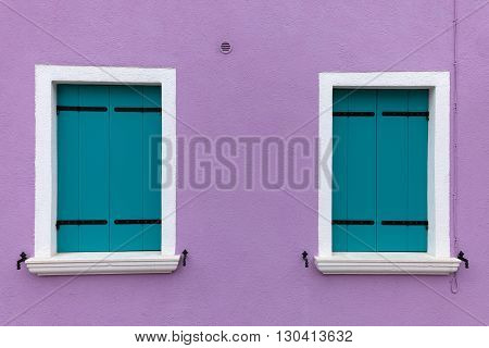 Picturesque two old windows with light blue shutters on light violet wall (Burano island Venice Italy)