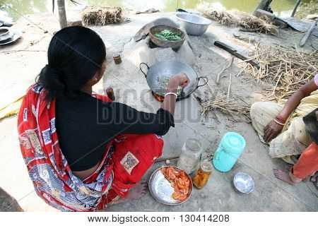 KUMROKHALI, INDIA - JANUARY 17: Traditional way of making food on open fire in old kitchen in a village, Kumrokhali, West Bengal, India January 17, 2009.