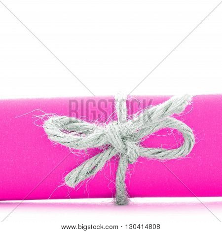 Handmade natural string knot tied on pink message roll, isolated