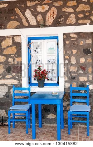 Blue table and chairs for two in front of stone wall Santorini island Greece