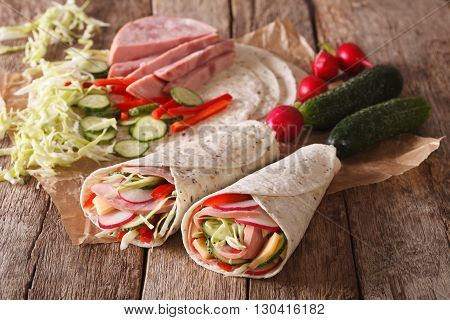 Sandwich Rolls With Ham, Cheese And Vegetables Close-up And Ingredients. Horizontal
