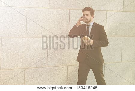 Toned picture of businessman eating junk food and e walking along street to office.