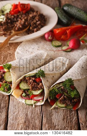 Tortilla Roll With Beef And Vegetables Close-up And Ingredients. Vertical
