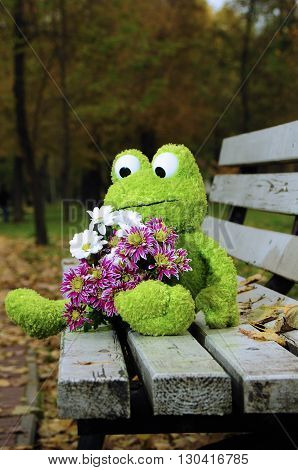 Toy frog with flowers sitting on a bench in nature