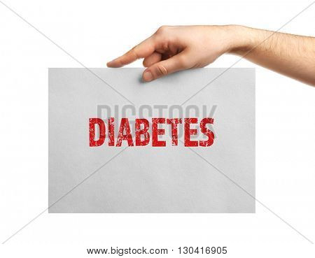 Male hand holding sheet of paper with text diabetes, isolated on white