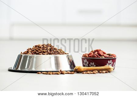 Pet food in metal bowls on a floor.