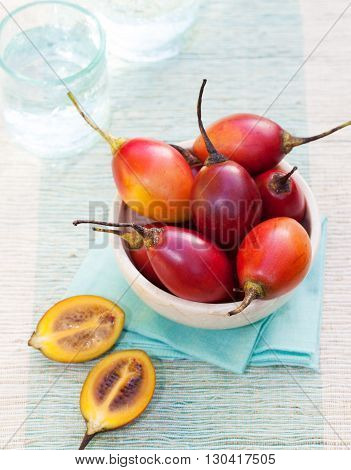 Tamarillo fruits with slice on blue napkin Outdoor background
