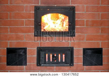 Brick oven with fire in the furnace door closeup photo