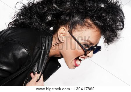 Furious young woman screaming with sunglasses and black leather jacket jn white background