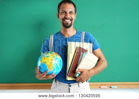 Geography teacher. Photo adult man with books and globe creative concept with Back to school theme