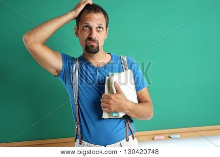 Confused adult student remember something. Photo adult man near blackboard education concept