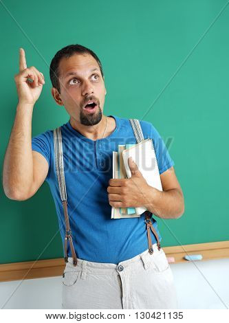 Adult student holding books in his hand and finger pointing up. Photo adult teacher near blackboard education concept