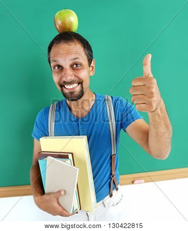 Cheerful teacher with an apple on her head showing thumbs up. Photo adult teacher near blackboard education concept