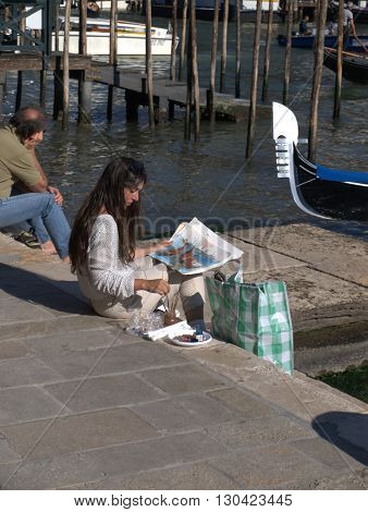 VENICE,ITALY - SEPTEMBER 23,2014 - The artist paints the gondola in the canals of Venice.