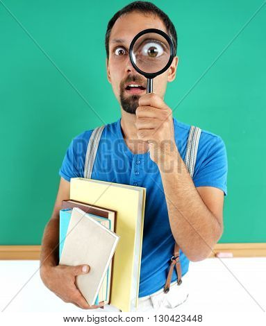 Man open-eyed with magnifier among the books. Photo of smiling teacher creative concept with Back to school theme