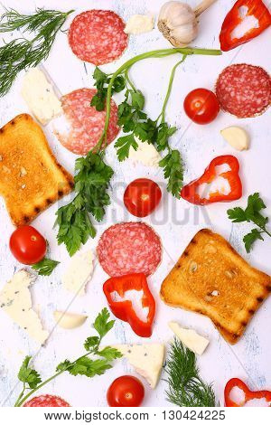 Fresh vegetables, crispy croutons and salami on white wooden table.