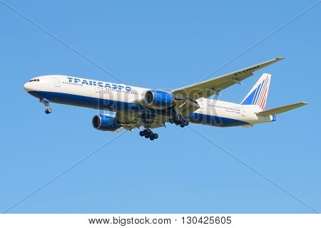 SAINT PETERSBURG, RUSSIA - AUGUST 21, 2015: The Boeing 777-312 (EI-UNM) of the company Transaero before landing in Pulkovo airport