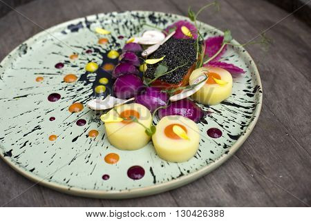 Fleur cuisine. Salmon with black caviar on a cuttlefish ink