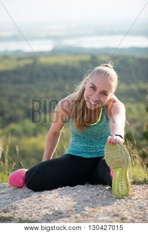 Fit woman stretching her leg to warm up outdoor.