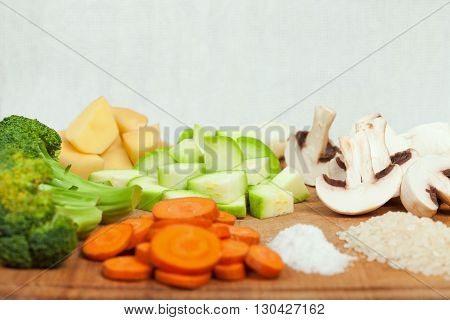 Fresh sliced soup ingredients laids on wooden cutting board. Side view low aperture shot selective focus