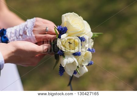 Groom and the bride with a bouquet of roses. Bride with groom holding wedding bouquet at ceremony. Wasp bee on a rose bud.