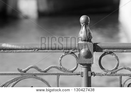 fragment of the top part of an iron ancient fence or protection closeup in retro style on an indistinct background of monochrome tone