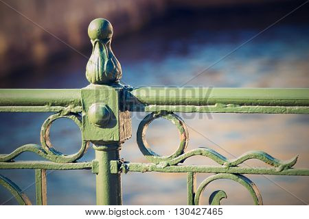 fragment of the top part of an iron ancient fence or protection closeup in retro style on an indistinct background