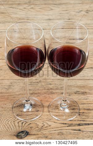 Two glass glasses with red wine standing next to an old wooden table