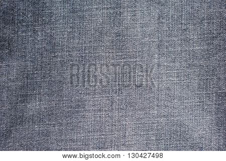 the textured background from rough cotton material or denim of pale color