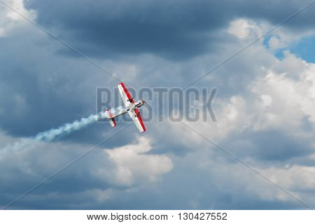Red - white plane jets of fumes in flight in a blue sky close-up
